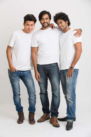 casual men: Smiling Indian young male friends on white background.