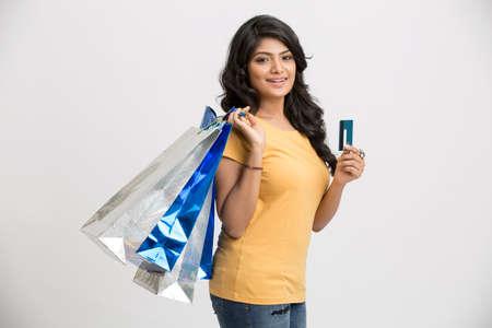 mujer alegre: Feliz mujer joven indio con bolsas de compra y la tarjeta de cr�dito Foto de archivo