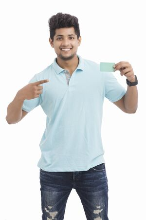 Young man showing business card on white. Stock Photo