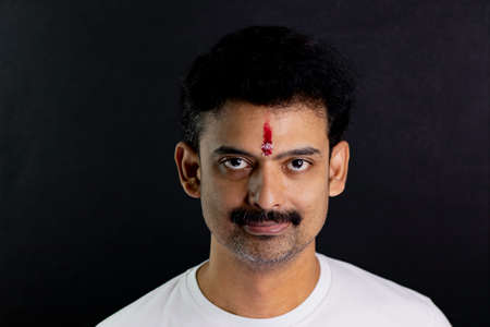 A man with festival tikli on forehead with isolated black background Imagens