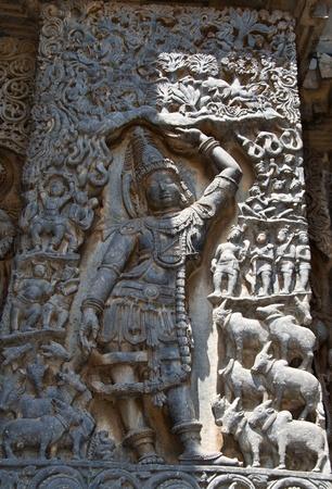 Krishna lifting Govardhana mountain to protect his people and cows; carved in Hoysaleshwara temple at Halebidu, Hassan district, Karnataka state, India, Asia