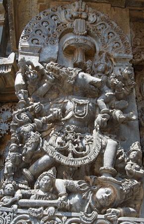 soapstone: Vishnu in Varaha avatar killing demon Hiranyaksha by crushing his head to protect Bhoodevi (mother earth); wall carving in Hoysaleshwara temple at Halebidu, Hassan district, Karnataka state, India, Asia Stock Photo