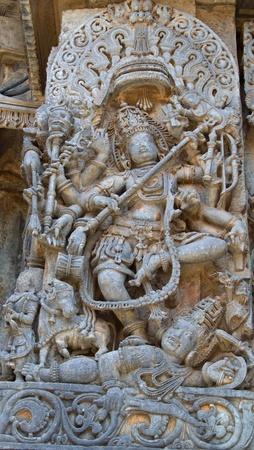 Lord Shiva killing a demon; carving in Hoysaleshwara temple at Halebidu,  Hassan district, Karnataka state, India, Asia Stock Photo