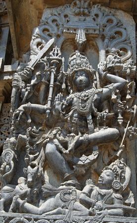 soapstone: Lord Shiva killing a demon with Nandi overlooking in Hoysaleshwara temple at Halebidu, Hassan district, Karnataka state, India, Asia