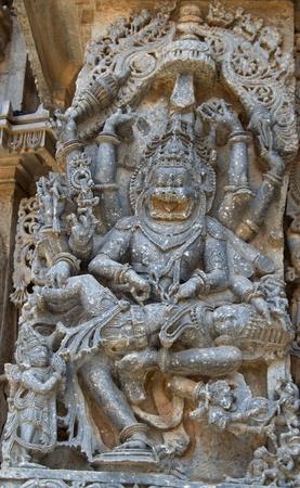 vishnu: Lord Vishnu in Narasimha avatar killing Hiranyakashipu; son Prahlada praying to lord; wall carving in Hoysaleshwara temple at Halebidu