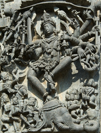 guise: Shiva killing a demon Gajasura appearing in the guise of an elephant by dancing inside and piercing its skin; wall carving in Channakeshava temple at Belur, Hassan district, Karnataka state, India, Asia
