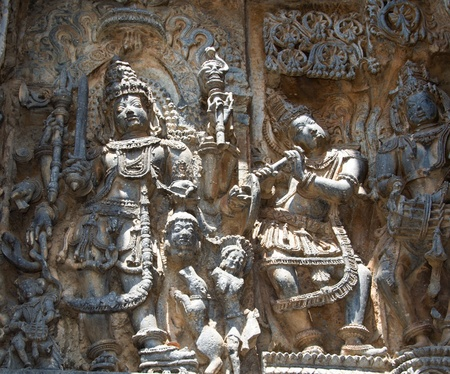 soapstone: Karthikeya killing a demon and holding his head in hand; dog sucking the blood to stop birth of another demon; carved on the walls of Hoysaleshwara temple at Halebidu, Hassan district, Karnataka state, India, Asia Stock Photo
