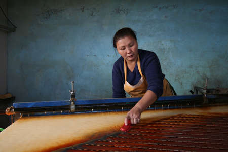 artisanal: woman working on shaker gold table Editorial