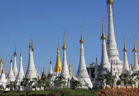 A field of white pagodas situated on an island in Inle lake, Myanmar  The sky is spotlessly blue  photo