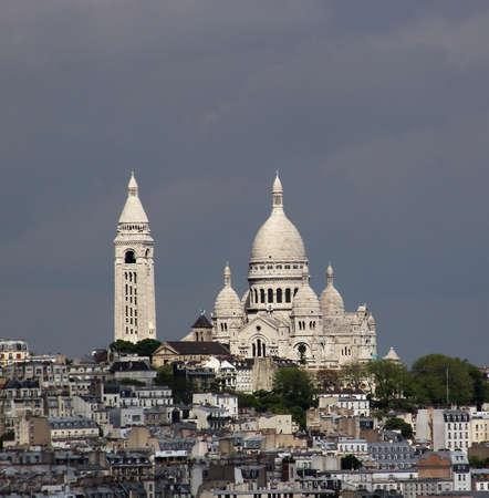 iluminados: La catedral de Sacre Coeur en el Mont Martre está iluminado por el sol y brilla brillantemente contra el cielo oscuro La foto fue tomada desde la parte superior del Arco del Triunfo