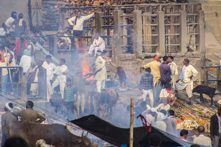 obscuring: The famous  Burning ghats of Varanasi. The smoke of the funeral pyres is obscuring the sight.