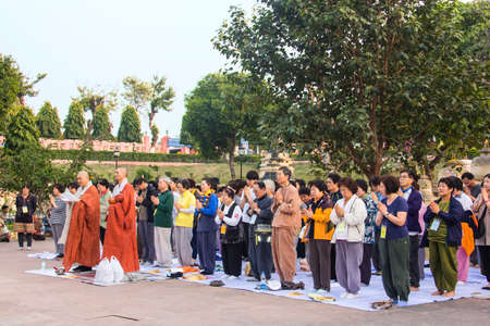 believers: A group of buddhist believers praying near Mahabodhi temple, India Editorial
