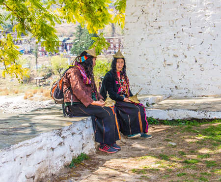 arunachal pradesh: Two nomad woman are sitting outside the dzong of Punakha,  Bhutan, trying to sell hats  They are wearing the typical nomad costume