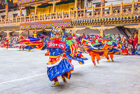 tantric: masked dancers at  drupchen festival in the dzong of Punakha, Bhutan. Drupchen festival is taking place yearly in march.  In the background are bhutanese spectators, watching the performance.