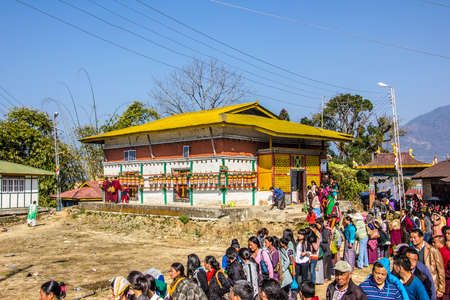 believers: At the bumchu festival, Tashiding, Sikkim, Buddhist believers, men and women,  are queuing in two lines to get into the temple  In the back is a beautiful temple with many prayer wheels