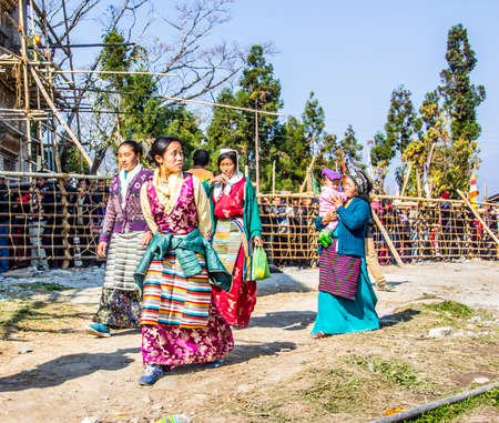 believers: Four women at the bumchu festival, Tashiding, Sikkim  In the background buddhist believers, men and women, are queuing in two lines to get into the temple