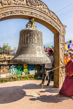 monch: A monch at bumchu festival, Tashiding, Sikkim, is ringing the big prayer bell  In the background are prayer flags and mani stones  Editorial