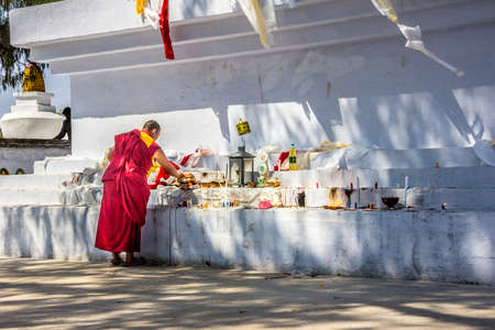 monch: A monch at bumchu festival, Tashiding, Sikkim, isworshipping the buddha at a big Stupa  chorten, choerten  Editorial