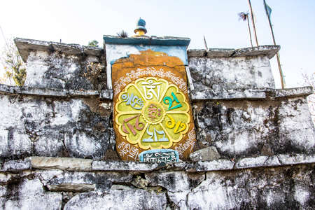 Dharma wheel, a symbol of constant change, engraved in a stone on a mani wall in Tashiding, Sikkim, India. photo