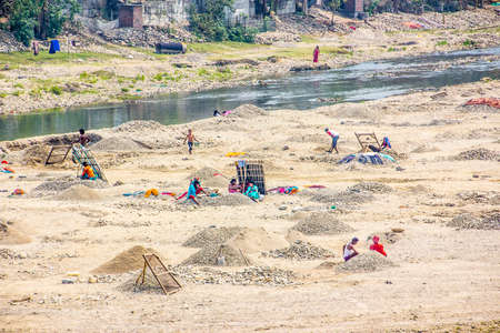 riverbed: Siliguri, West Bengal, India: people are sieving gravel in a dry riverbed, to make some money. Editorial