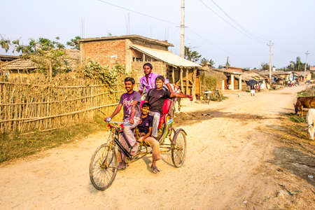 four boys on a bicycle rikshaw in the outskirts of Janakpur, nepal, are having fun