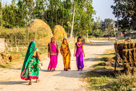 the fruitful: Beautiful women in colorful sarees are walking along a dirt road in the Terai, the most southern, warm and fruitful part of Nepal Editorial