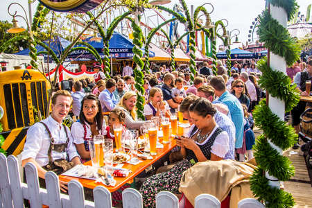Oktoberfest munich  People dressed in traditional costumes are sitting in the beergarden  報道画像