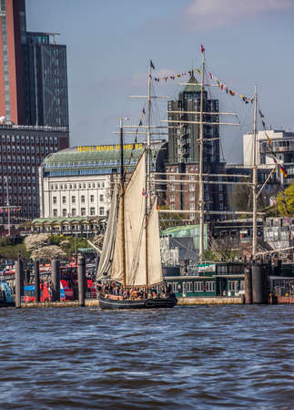 View from the harbor to the city of Hamburg, Germany. In the foreground is a historic sailboat.