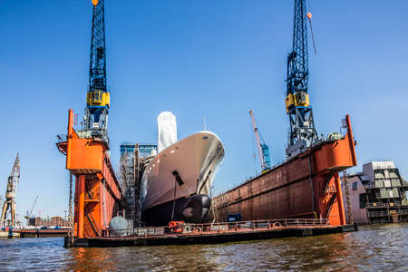 drydock: A big containership is lying in the drydock, in the harbor of Hamburg, Germany.