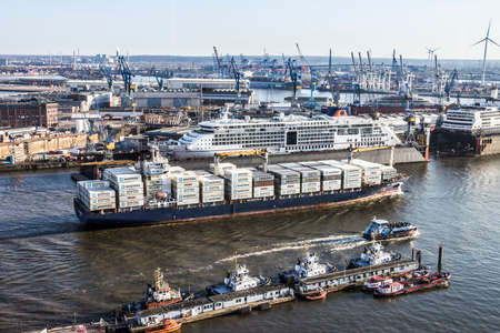 containership: A large containership is leaving the harbor of Hamburg, Germany. Behind is a large passenger boat lying in a drydock Editorial