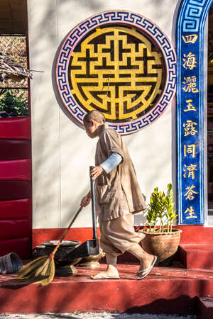 fang: A chinese monk in a chinese temple near Fang, is cleaning the floor.