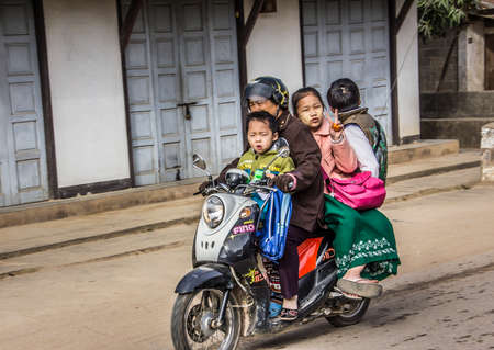 streetscene: Typical Myanmar streetscene with a whole family on a motor scooter.
