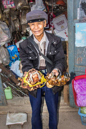 shamanic: a maret seller is presenting  a tiger paw and skull as shamanic medicine on the market of Keng Tung Myanmar Editorial