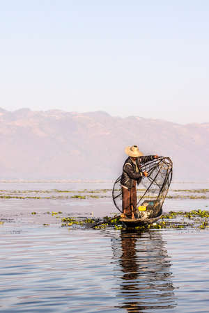 moutains: A fisherman at Inle lake iscatching fish in a big fish trap. In the background are the moutains