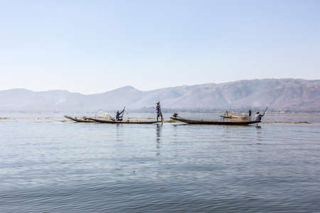 stilt: A legrowing fisherman at Inle lake is catching fish with a net .