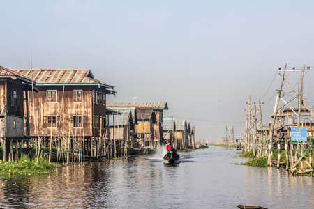 stilted: A boat is speeding through the main road of a stilt village at the Inle lake, Myanmar.