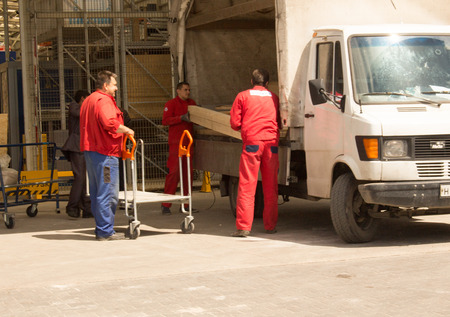 movers in red suits the car loaded Editorial