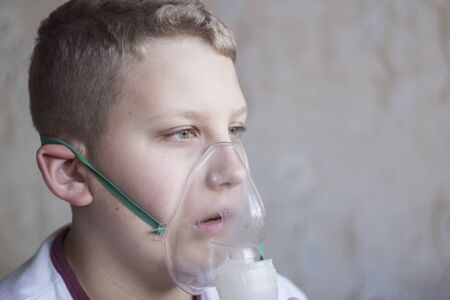 the boy with white hair breathing in the inhaler