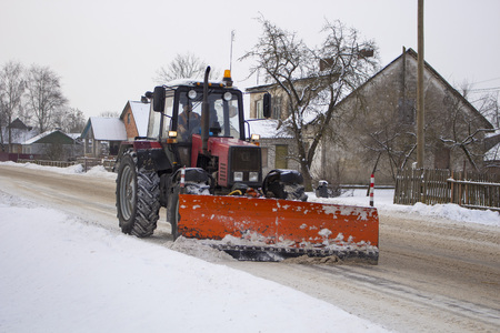 red tractor clears the road from snow