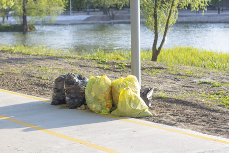 ecology.yellow garbage bags are near the road