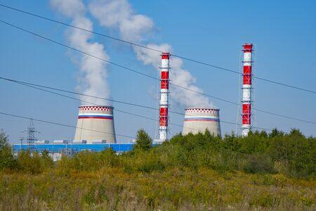 the smoky chimneys of the power plant stand against the blue sky Reklamní fotografie