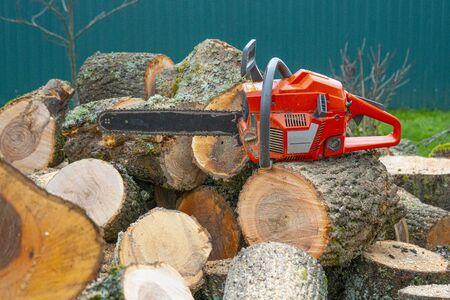 orange chainsaw lying on a log