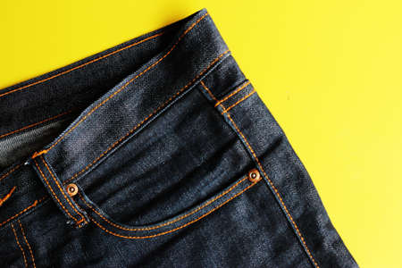 jeans yellow background. Imagens
