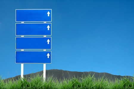 roadsign with green grass and blue sky photo