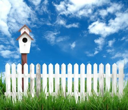 white picket fence: birdhouse with white fenceand blue sky Stock Photo