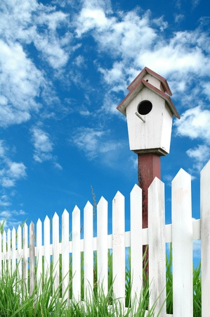 witte hek met birdhouse en blue sky Stockfoto
