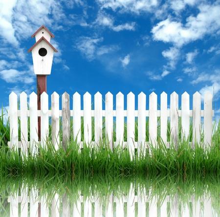 Birdhouse con valla de blanco y azul cielo