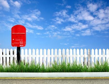 cerca blanca: Postbox con valla de blanco y azul cielo