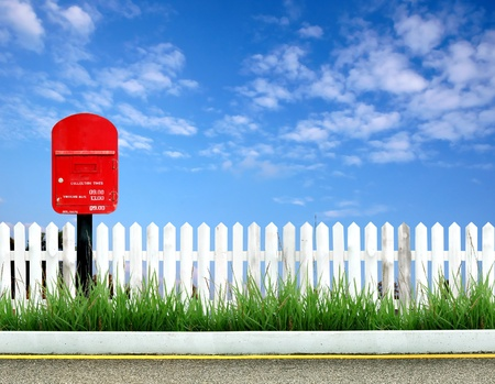 postbox with white fence and blue sky Stock Photo