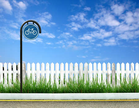 picket fence: bicycle sign and white fence and blue sky